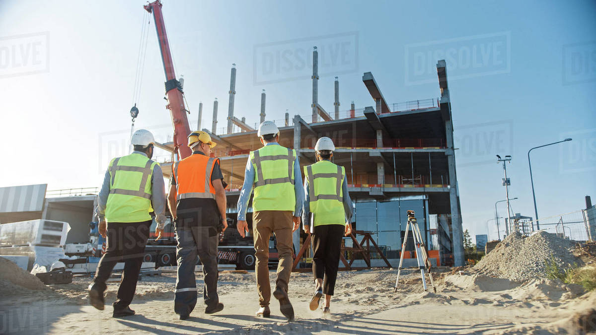 Diverse Team of Specialists Inspect Commercial, Industrial Building Construction Site. Real Estate Project with Civil Engineer, Investor and Worker. In the Background Crane, Skyscraper Formwork Frames Royalty-free stock photo