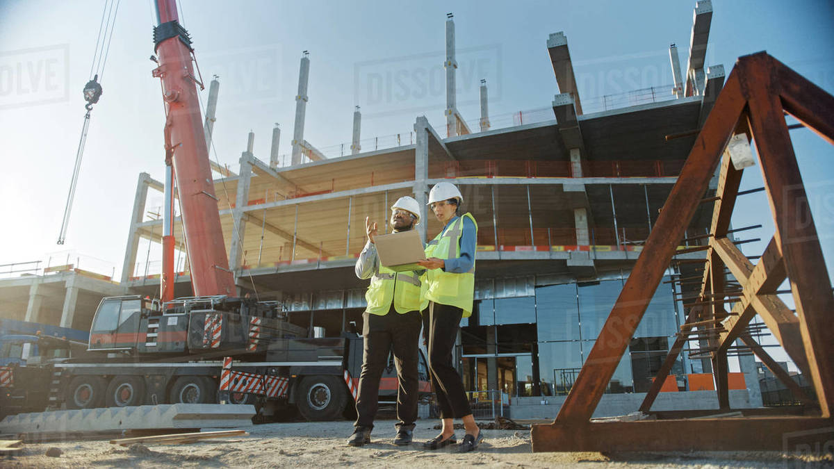 Two Specialists Inspect Commercial, Industrial Building Construction Site. Real Estate Project with Civil Engineer, Investor Use Laptop. In the Background Crane, Skyscraper Concrete Formwork Frames Royalty-free stock photo