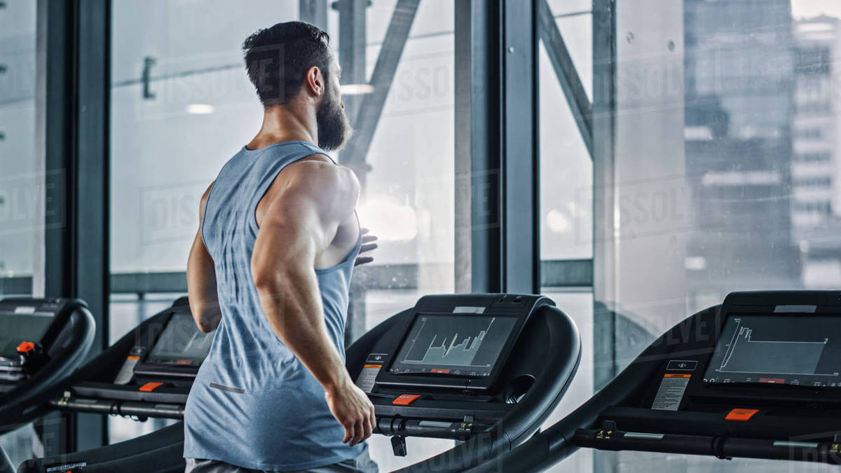 Athletic Muscular Man Running on a Treadmill, Leg and Cardio Day. Strong Man Training in the Modern Gym Fitness Club. Back View Shot  Royalty-free stock photo