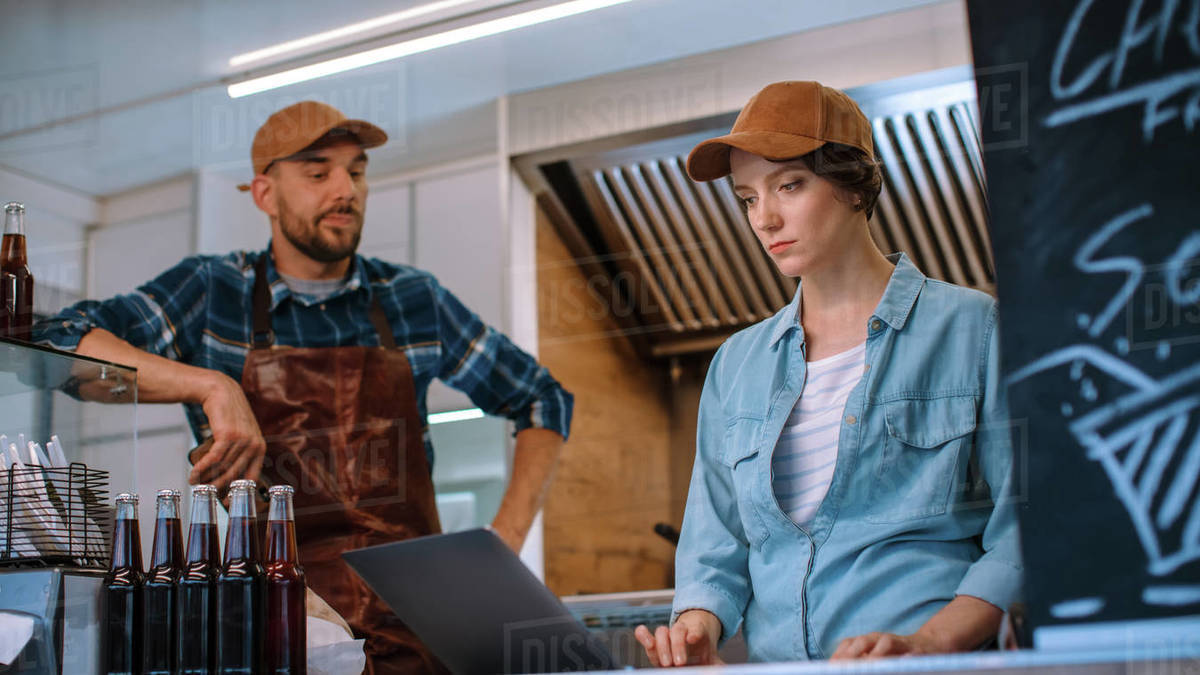 Successful Food Truck Employees in Brown Caps. Female is Using Laptop Computer in their Commercial Truck or Kiosk Selling Street Food and Drinks. Royalty-free stock photo