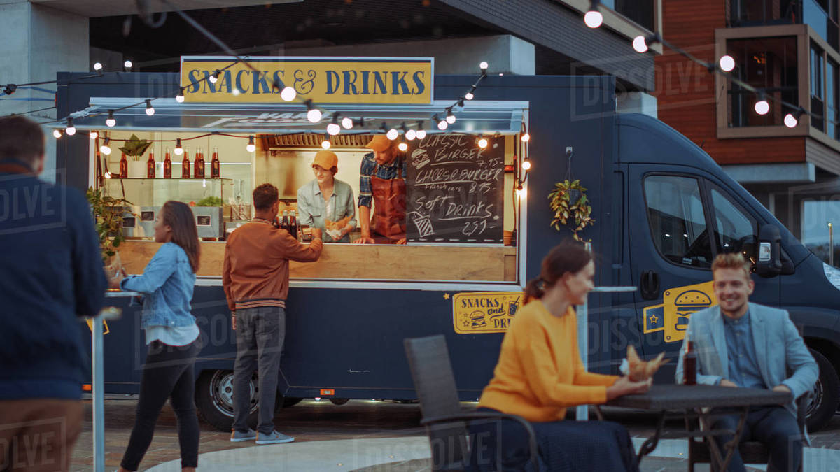 Food Truck Employee Hands Out a Card Card Terminal For Contactless Payment to Happy Young Hipster Customer, who is Buying a Tasty Burger. Commercial Truck Selling Street Food in a Modern Cool Neighbourhood. Royalty-free stock photo