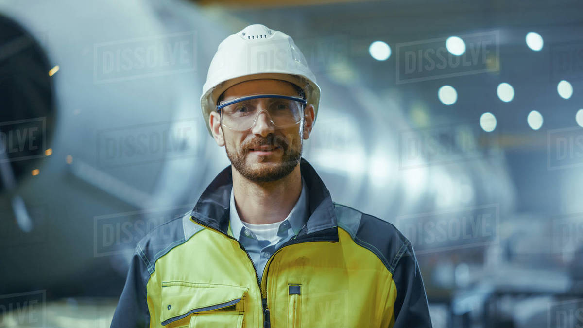 Portrait of Smiling Professional Heavy Industry Engineer / Worker Wearing Safety Uniform, Goggles and Hard Hat. In the Background Unfocused Large Industrial Factory where Welding Sparks Flying Royalty-free stock photo