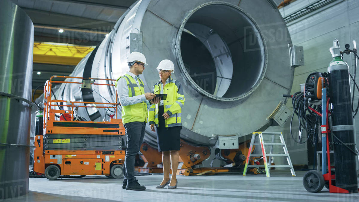 Two Heavy Industry Engineers Stand in Pipe Manufacturing Factory, Use Digital Tablet Computer, Have Discussion. Facility for Construction of Oil, Gas and Fuel Pipeline Transportation Products Royalty-free stock photo