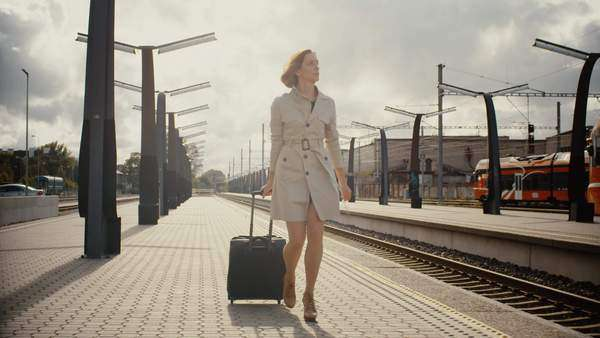 Woman with luggage walking in railway station Royalty-free stock video