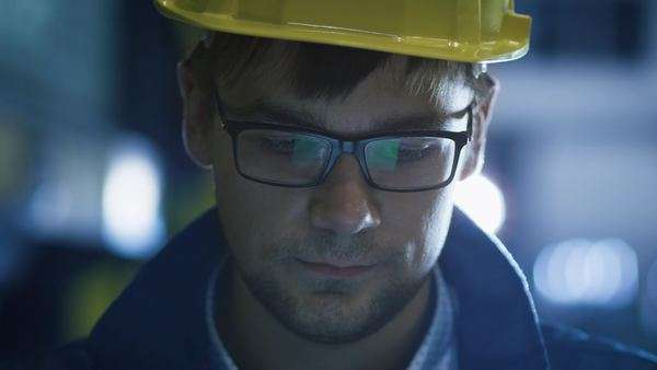 Technician in glasses and hard hat using tablet in industrial environment. Royalty-free stock video