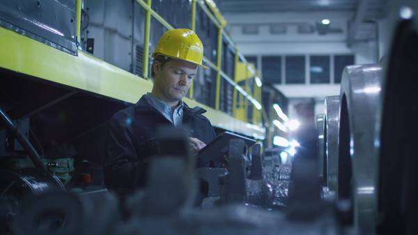 Technician in hard hat using tablet in industrial environment. Royalty-free stock video