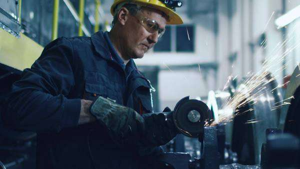 Worker with angle grinder does metalworking in industrial environment Royalty-free stock video