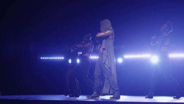 Man in a hoodie leads a group of dancers while singing on a dark stage with lights. Royalty-free stock video