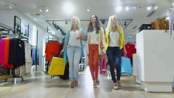 Three cheerful young women are walking through a department store in colorful garments. Royalty-free stock video