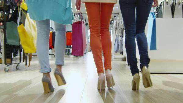 Low shot of three girls that are walking through a clothing store in colorful garments. Royalty-free stock video