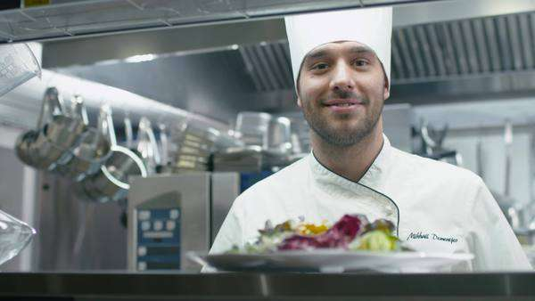 Happy professional chef in a commercial kitchen is serving salad. Royalty-free stock video