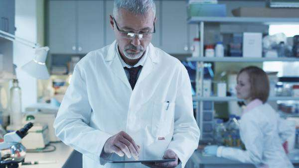 Senior scientist is walking with a tablet in a laboratory where colleagues are working. Royalty-free stock video