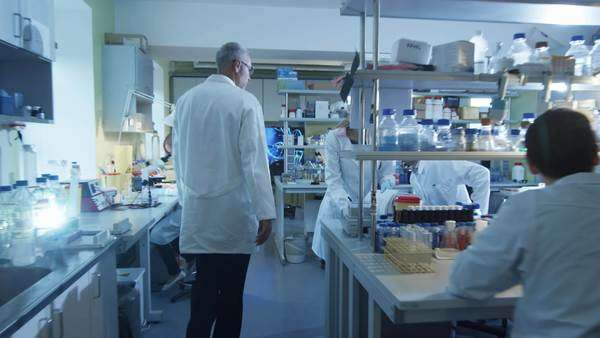 Senior scientist in white coat is greeting collegues in a laboratory. Royalty-free stock video