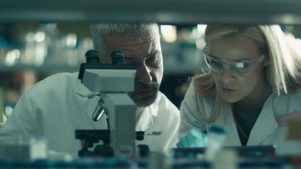 Male and female scientist are working with a microscope and a tablet in a laboratory. Royalty-free stock video
