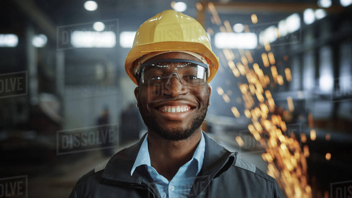Portrait Shot of Happy Professional Heavy Industry Engineer/Worker Wearing Uniform, Glasses and Hard Hat in Steel Factory and Smiling on Camera. Industrial Specialist in Metal Construction Manufacture Royalty-free stock photo