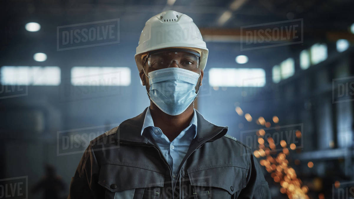 Professional Heavy Industry Engineer/Worker Wearing Safety Face Mask, Uniform, Glasses and Hard Hat in a Steel Factory. African American Industrial Specialist Standing in Metal Construction Facility. Royalty-free stock photo