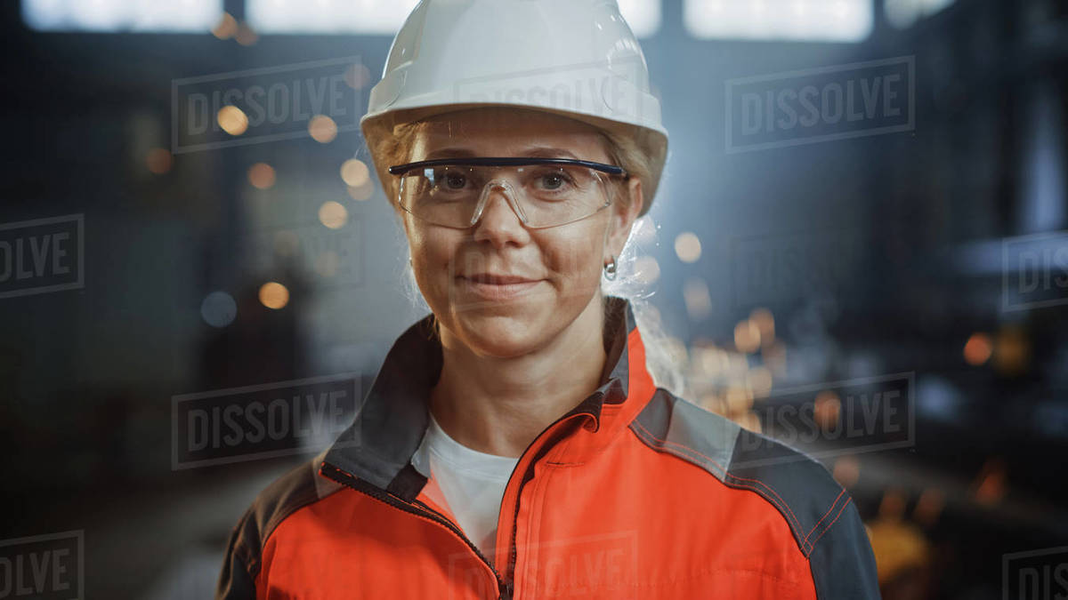 Portrait of a Professional Heavy Industry Engineer Worker Wearing Uniform, Glasses and Hard Hat in a Steel Factory. Beautiful Female Industrial Specialist Standing in Metal Construction Facility. Royalty-free stock photo