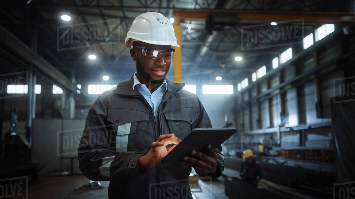Professional Heavy Industry Engineer Worker Wearing Safety Uniform and Hard Hat Uses Tablet Computer. Smiling African American Industrial Specialist Walking in a Metal Construction Manufacture. Royalty-free stock photo