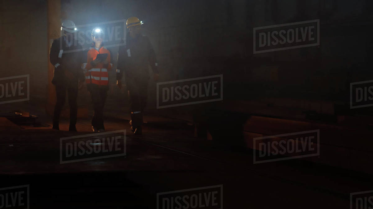 Three Diverse Multicultural Heavy Industry Engineers and Workers in Uniform Walk in Dark Steel Factory Using Flashlights on Their Hard Hats. Female Industrial Contractor is Using a Tablet Computer. Royalty-free stock photo