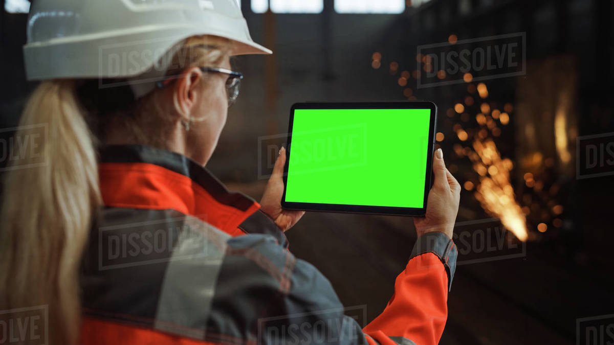 Professional Heavy Industry Engineer Uses Tablet Computer with Green Screen Mock Up Display. Female Industrial Specialist Working in a Metal Manufacture Warehouse with Sparks in the Background. Royalty-free stock photo