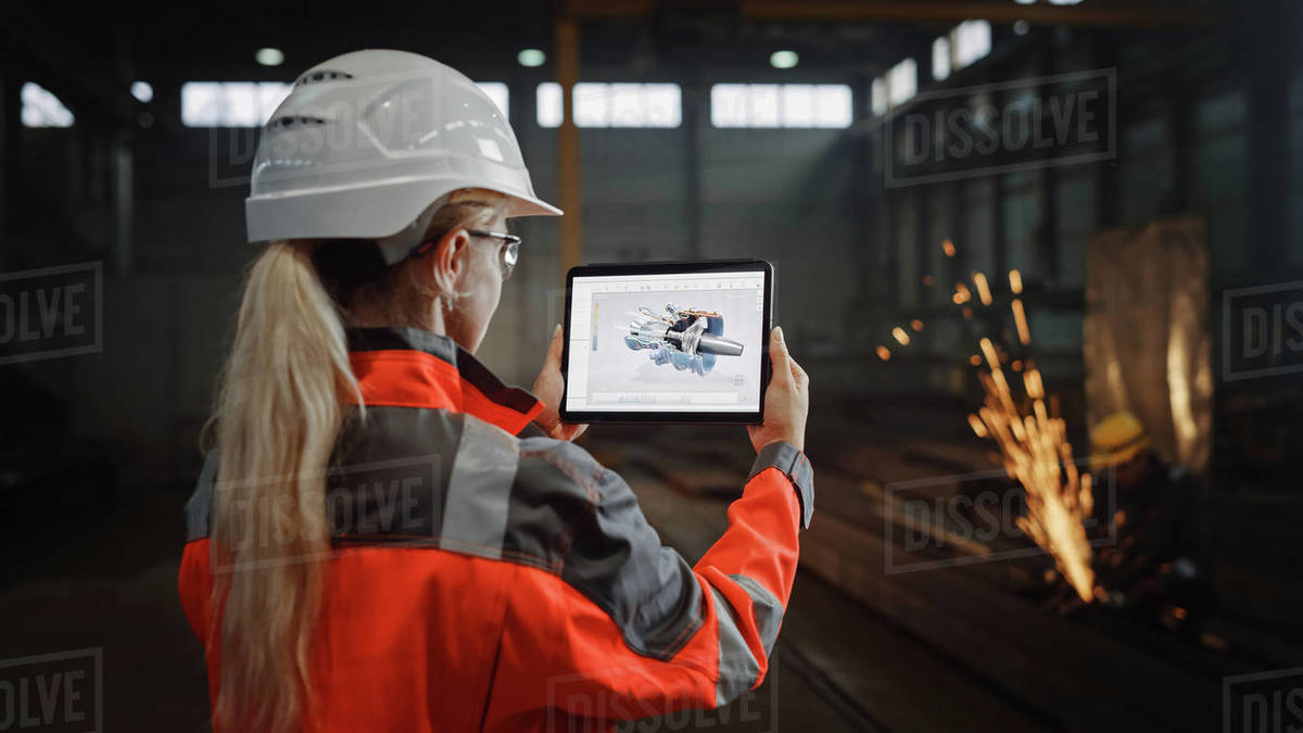 Professional Heavy Industry Engineer Uses Tablet Computer for Augmented Reality Render with Interactive Turbine Engine Blueprint. Female Industrial Specialist Working in a Metal Manufacture Warehouse. Royalty-free stock photo
