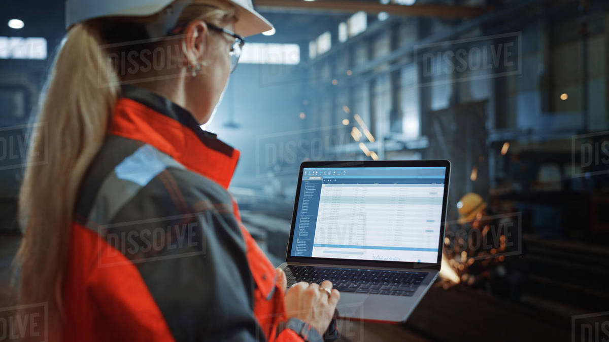 Professional Heavy Industry Engineer Uses Laptop Computer with Administrative Data Cataloging Software. Female Industrial Specialist Working in a Metal Manufacture Warehouse. Royalty-free stock photo