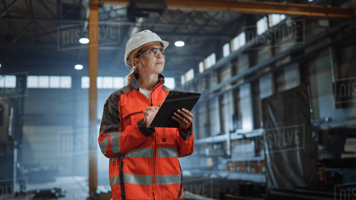 Professional Heavy Industry Engineer Worker Wearing Safety Uniform and Hard Hat, Using Tablet Computer. Serious Successful Female Industrial Specialist Walking in a Metal Manufacture Warehouse. Royalty-free stock photo