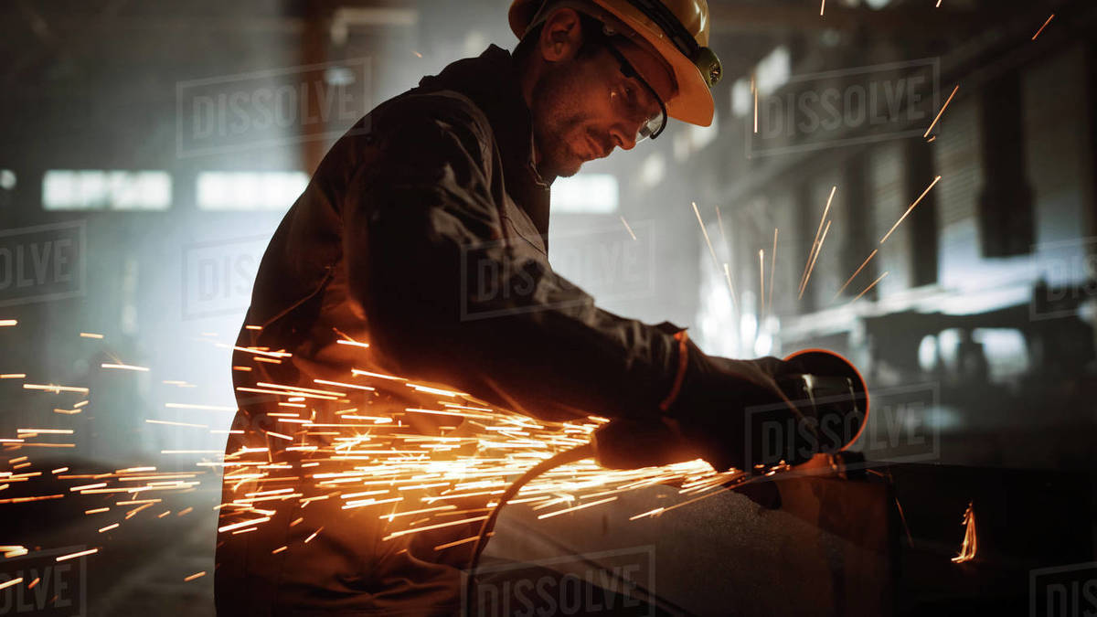 Heavy Industry Engineering Factory Interior with Industrial Worker Using Angle Grinder and Cutting a Metal Tube. Contractor in Safety Uniform and Hard Hat Manufacturing Metal Structures. Royalty-free stock photo