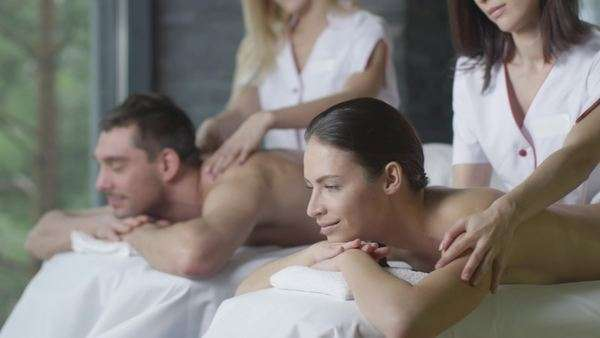 Young couple is getting a relaxing massage from female masseurs in wellness center. Royalty-free stock video