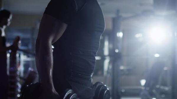 Handsome fit sporty man does dumbell curl exercises in dark gym. Royalty-free stock video