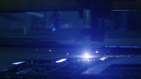 Close-up shot of a CNC plasma cutter that is cutting out metal objects in a heavy industry factory. Royalty-free stock video