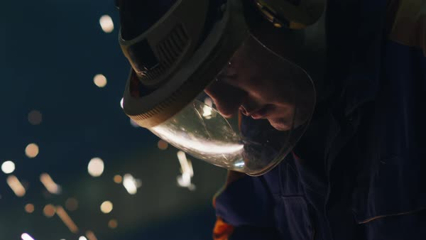 Portrait of a heavy industry worker in a mask that reflects sparks while he is working with metal on a angle grinder. Royalty-free stock video