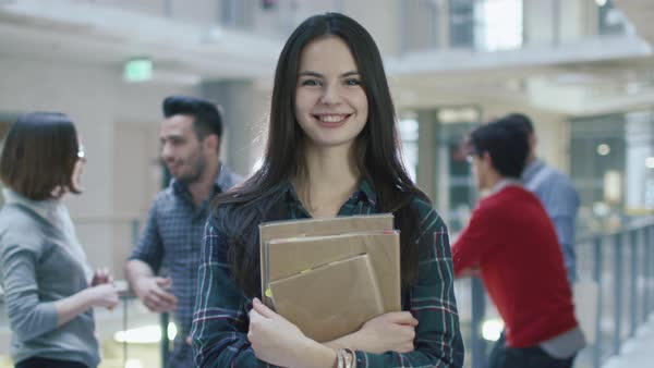Portrait of a young pretty brunette student girl in an high school hallway. Royalty-free stock video