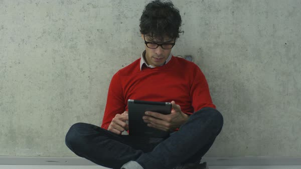 Young man students is sitting on the floor in a college hallway and using a tablet computer. Royalty-free stock video