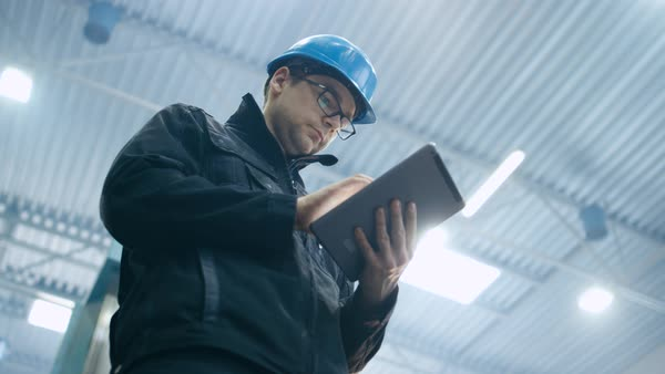 Factory worker in a hard hat is using a tablet computer. Royalty-free stock video