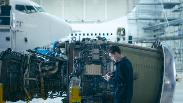 Aircraft maintenance mechanic inspecting and working on airplane jet engine in hangar Royalty-free stock video