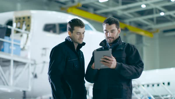 Aircraft maintenance workers having conversation. Holding and using tablet. Royalty-free stock video