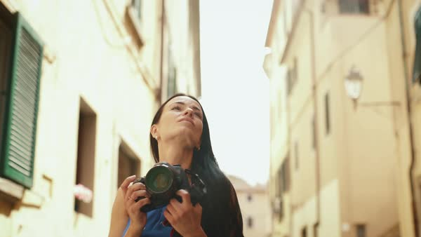 Attractive young brunette woman in light summer dress walking and taking pictures with her professional camera on streets of European town. Royalty-free stock video