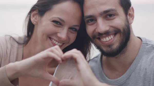 Happy smiling attractive couple forming hearth sign with their hands. Royalty-free stock video
