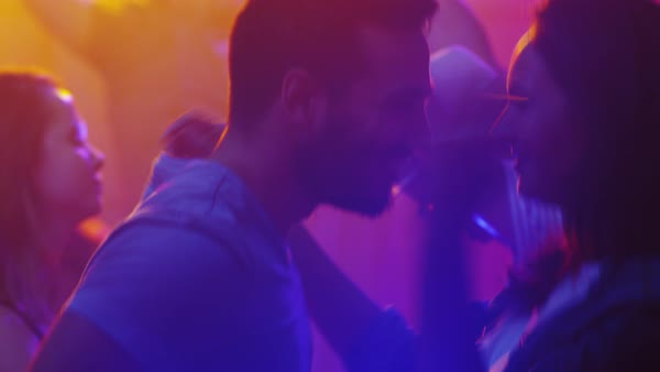 People dancing, having fun and raising hands in nightclub, young man and woman dancing together. Royalty-free stock video