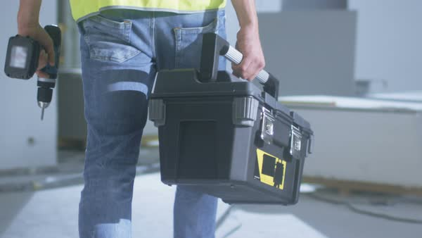 Construction worker walking inside building under construction and carrying toolbox Royalty-free stock video