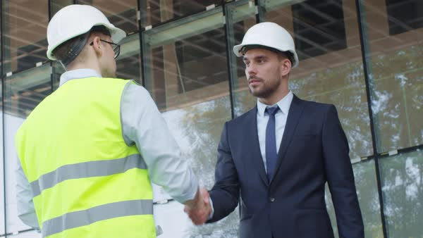 Businessman and engineer in hard hats having agreement handshake on construction site. Royalty-free stock video