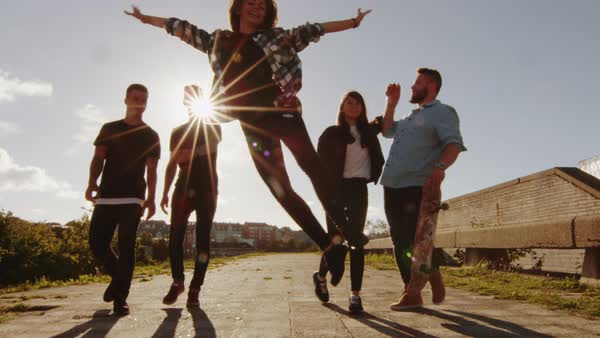 Group of happy teenagers laughing, raising hands, jumping while moving forward towards camera. Royalty-free stock video