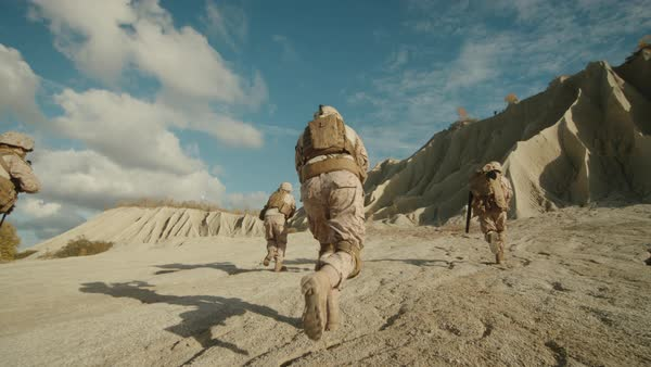 Follow Shot of Squad of Soldiers Running Forward During Military Operation in the Desert. Slow motion. Royalty-free stock video