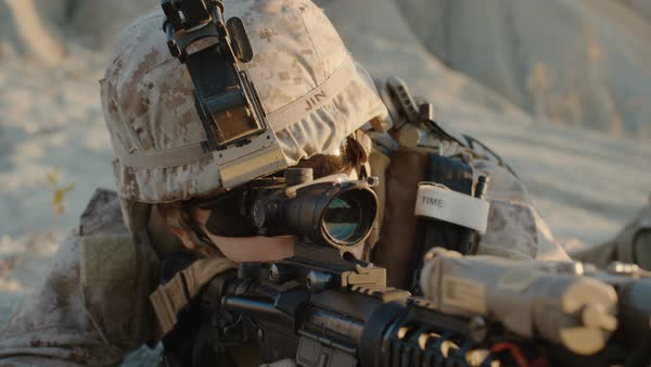Close-up of Soldier Lies Down on the Hill, Aims through the Assault Rifle Scope in Desert Environment. Slow Motion. Royalty-free stock video