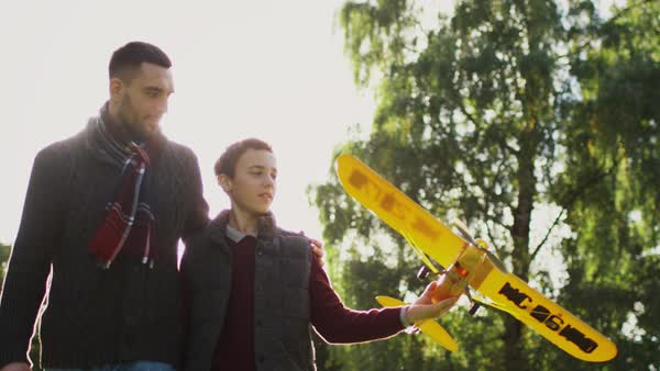 Father and son walking in the park with model airplane. Son twists propeller Royalty-free stock video