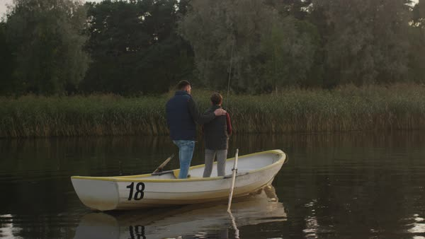 Father and son are standing in the boat while fishing. Son swings fishing rod and father encourages son Royalty-free stock video