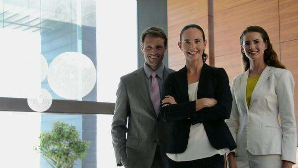 Portrait of a businessman and two businesswomen turning head to face camera and smiling. Royalty-free stock video
