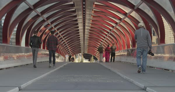 Slow motion shot of pedestrians walking on Peace Bridge in Calgary Royalty-free stock video