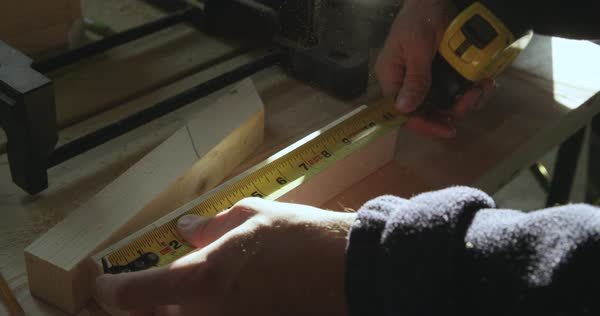 Slow motion shot of a carpenter using measuring tape to mark section of wood Royalty-free stock video